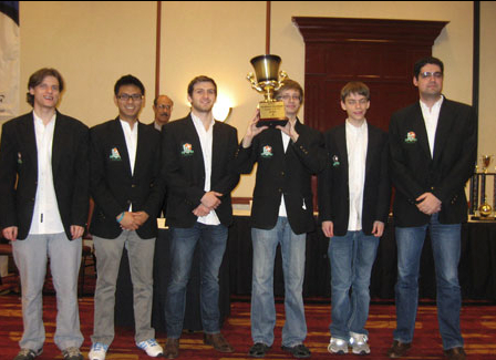 "UT Dallas ""A"" team (left to right): GM Valentin Yotov, GM Julio Sadorra, TD Guadalupe in background, GM Cristian Chirila, IM Salvijus Bercys, IM Conrad Holt & IM Milos Pavlovic"